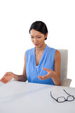 Young businesswoman gesturing while sitting at table Royalty Free Stock Photo