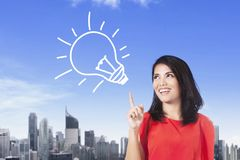 Young businesswoman with bulb symbol Stock Images
