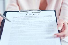 Young businesswoman giving contract for you to sign. Just Hands over the table. Young businesswoman giving contract for you to sign royalty free stock image