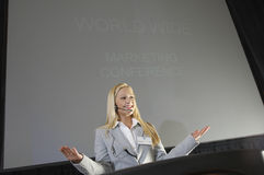 Young Businesswoman Giving A Lecture. Low angle view of a happy young businesswoman giving a lecture at business conference Stock Photos