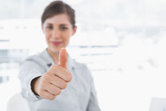 Young businesswoman giving thumb up and smiling Stock Image