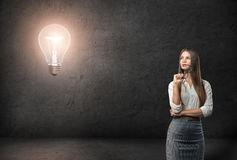 Young businesswoman with glasses looking thoughtfully on the glowing light bulb royalty free stock photos