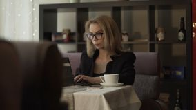 Young businesswoman in glasses typing on keyboard notebook at couch in cafe. Young businesswoman in glasses typing on keyboard notebook sitting at couch in cafe stock footage