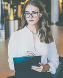 A young businesswoman with glasses and a white shirt is standing and holding a clipboard. The girl is making notes. Royalty Free Stock Photos