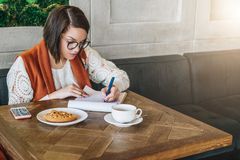 Young businesswoman in glasses and white sweater is sitting in cafe at table, working. Girl fills out an application Stock Photography