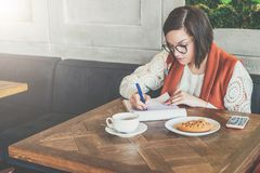 Young businesswoman in glasses and white sweater is sitting in cafe at table, working. Girl fills out an application Royalty Free Stock Images