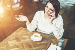 Young businesswoman in glasses and white sweater is sitting in cafe at wooden table and talking on cell phone. Telephone conversations. Hipster girl freelancer Royalty Free Stock Photography