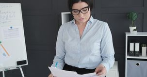 Young businesswoman in glasses at work. Businesswoman doing paperwork at workplace stock video