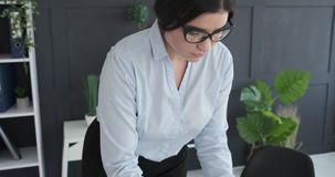 Young businesswoman working at office. Young businesswoman in glasses working at office stock video footage