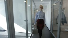 Young businesswoman is going throught the corridor in modern bright office. Blond female manager is wearing blue shirt and dark skirt and is holding notebook stock video footage