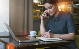 Young businesswoman in gray dress sitting at table in cafe, talking on cell phone while taking notes in notebook. Stock Photography