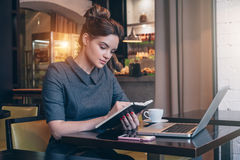 Young businesswoman in gray dress sitting at table in coffee shop and reading book. Stock Photo