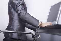 Young businesswoman handcuffed to her office chair Royalty Free Stock Image