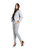 Young businesswoman with hands in pocket in elegant business stripped suit Stock Images