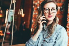 Young businesswoman has telephone conversations.Cheerful girl blogger in trendy glasses sitting in cafe,talking on phone. Young female entrepreneur has telephone royalty free stock photo