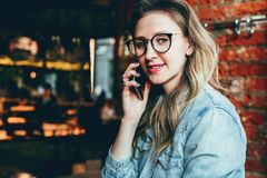 Young businesswoman has telephone conversations.Cheerful girl blogger in trendy glasses sitting in cafe,talking on phone. Young female entrepreneur has telephone royalty free stock photography