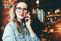 Young businesswoman has telephone conversations.Cheerful girl blogger in trendy glasses sitting in cafe,talking on phone. Young female entrepreneur has telephone stock photography