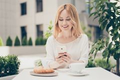 Young businesswoman having brunch at a cafe, using mobilephone,. Communicate with her lover through free wi fi Stock Image