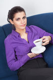 Young businesswoman having coffee break. Pretty young businesswoman having a coffee break in the office Stock Images