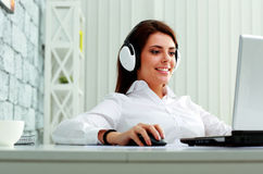Young businesswoman in headphones working on a laptop Royalty Free Stock Photography