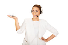 Young businesswoman in headset holding car toy Stock Photos