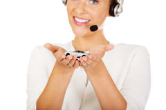 Young businesswoman in headset holding car toy Stock Image