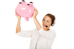 Young businesswoman in headset holding piggybank Stock Photos