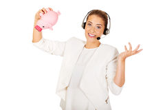 Young businesswoman in headset holding piggybank.  Stock Image