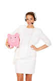 Young businesswoman in headset holding piggybank.  Royalty Free Stock Photography