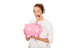 Young businesswoman in headset holding piggybank.  Stock Photos