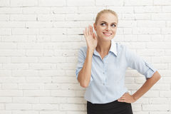 Young businesswoman hearing something Royalty Free Stock Images