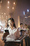 Young businesswoman with her cell phone, coworkers on the background, portrait Stock Photos