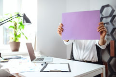 Young businesswoman hiding head behind paper at workplace in office. royalty free stock image
