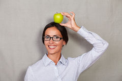 Young businesswoman holding apple on head Stock Image