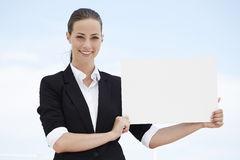 Young businesswoman holding blank sign Stock Photo