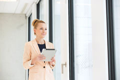 Young businesswoman holding digital tablet while looking away in office Stock Photo
