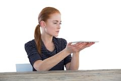 Young businesswoman holding digital tablet. While sitting at table against white background Stock Images