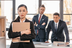 Young businesswoman holding folder and businessmen standing behind Stock Photos