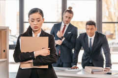 Young businesswoman holding folder and businessmen standing behind Royalty Free Stock Images
