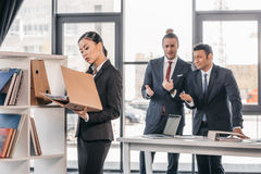 Young businesswoman holding folder while colleagues standing and looking behind Royalty Free Stock Photos