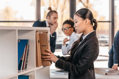 Young businesswoman holding folder while colleagues standing and looking behind Stock Photo