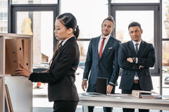 Young businesswoman holding folder while colleagues standing and looking behind Royalty Free Stock Photo