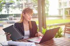 Young businesswoman holding ipad sitting on desk and looking away,Sun light morning time royalty free stock image