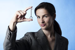 Young businesswoman holding key between fingers. Concept: The Key to Success, Close-up portrait of business woman holding key between fingers, focus on face Stock Photo