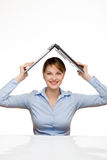 Young businesswoman holding a laptop. Above her head like a roof Stock Image