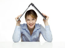 Young businesswoman holding a laptop. Above her head like a roof Stock Photography