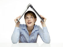 Young businesswoman holding a laptop. Above her head like a roof Royalty Free Stock Image