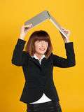 Young businesswoman holding laptop above head. Portrait of a beautiful, young businesswoman, holding a laptop above her head as a shelter, on yellow background royalty free stock photography