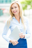 Young businesswoman holding laptop. Outdoors stock photos