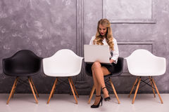 Young businesswoman holding laptop while sitting on chair Stock Photography